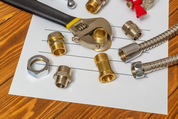 メモと修理計画の準備のために、シートに予備部品と調整可能なスパナのクローズアップを配管