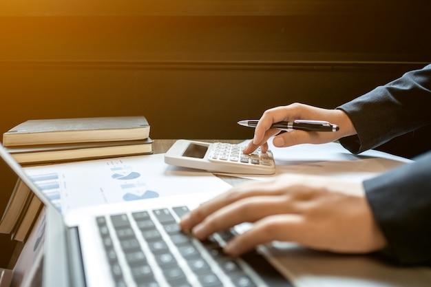 Финансовый инспектор, осуществляющий расчет инвестиционных данных с документами и ноутбуком