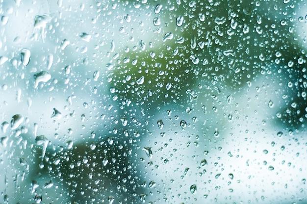 Дождь падает на оконное стекло, вода на зеркале, селективный фокус