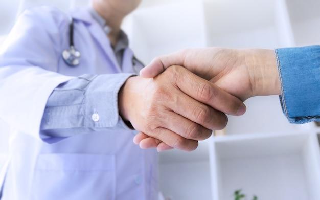 医者、コンサルタント、手、病院で患者と握手する