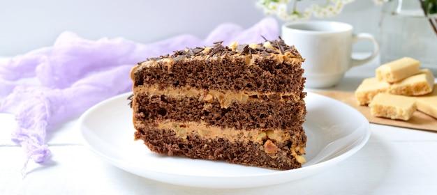 白い木製のテーブルにナッツクリームとチョコレートケーキ。皿の上のケーキと一杯のコーヒー。