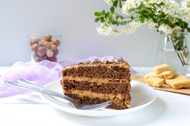 Шоколадный торт с ореховым кремом на белом деревянном столе. кусок торта на тарелку и чашку кофе.
