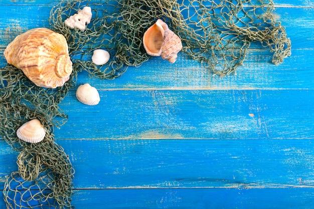 熱帯の海の背景。別の貝殻、青いボード上の古い漁網、トップビュー。碑文用の空き容量。夏のテーマ。