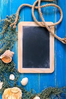 熱帯の海の背景。別の貝殻、青いボード上の古い漁網、トップビュー。スレートの碑文用の空き容量。夏のテーマ。