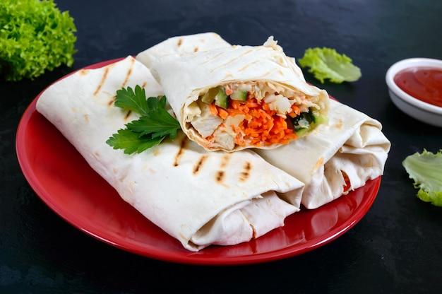 Вкусный бутерброд с шаурмой на черной поверхности. буррито обертывает с курицей-гриль и овощами, зеленью. фахитас, лаваш. традиционная ближневосточная закуска. мексиканская кухня