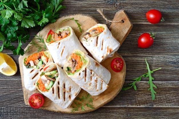 Свежие тортилья обертывания с курицей, грибами и свежими овощами на деревянной доске. курица мексиканская буррито. вкусная закуска. блюда из лаваша. концепция здорового питания.