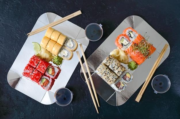 Набор суши роллы, соус, васаби и рука с палочками для еды на темном столе. меню суши-ресторана. различные виды суши. японская еда. вид сверху