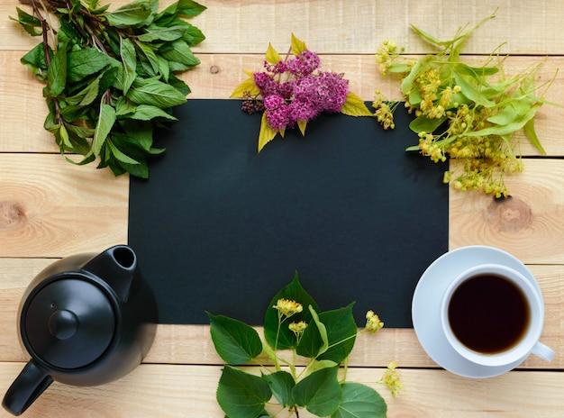 Каркасный травяной чай (мята, липа), чайник, чашка чая. внутри черная рамка - место для надписей. вид сверху.