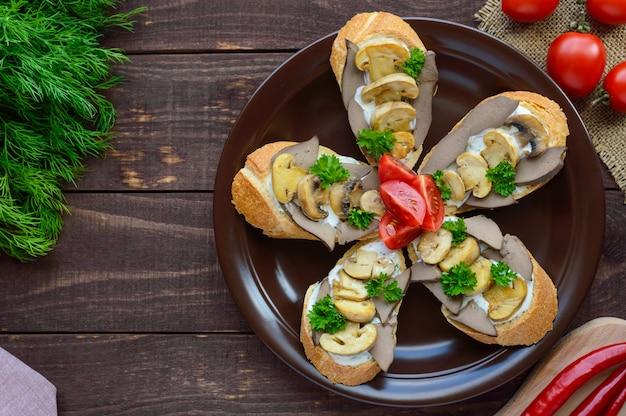 Бутерброды с грибами, печенью индейки и соусом тар-тар на хрустящем багете. вид сверху. диетический завтрак