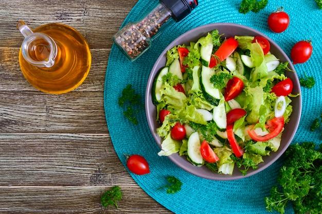 Вкусный витаминный диетический салат со свежими огурцами, помидорами, зеленью. салат из органических овощей. вид сверху, плоская планировка.