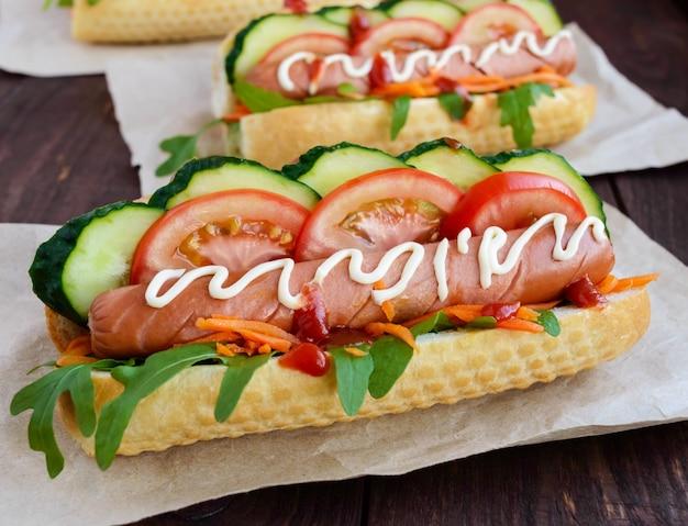 自家製のホットドッグと野菜、ジューシーなソーセージ、木製のテーブルにルッコラ。閉じる。