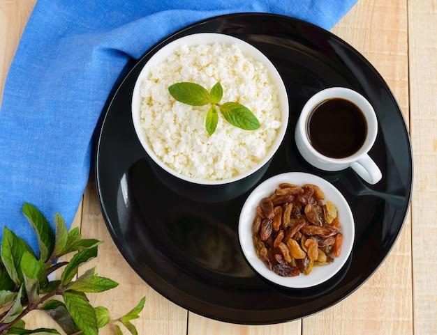 Свежий домашний творог, золотой изюм и чашка кофе. здоровый завтрак. вид сверху