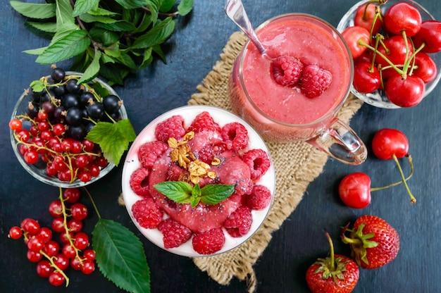 Вкусный полезный десерт: йогурт, свежие ягоды, мюсли, малиновый соус на черном.