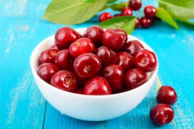 青い木製の背景に白いセラミックボウルで熟した赤い桜の果実。