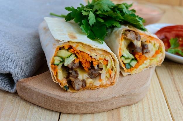 Шаурма с начинкой из мяса на гриле, соусом, овощами