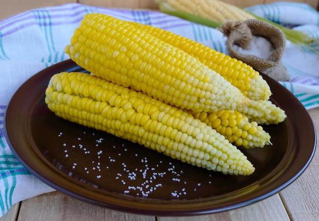Вареные початки сладкой кукурузы на глиняной тарелке