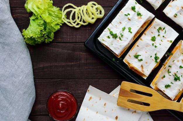 Слоеный пирог (пицца) из тонкого лаваша, фаршированный колбасой, грибами, сырным соусом. вид сверху