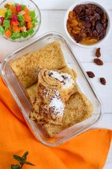 白い木製の背景のガラス容器にレーズンとカッテージチーズのおいしい繊細なパンケーキ。上面図。
