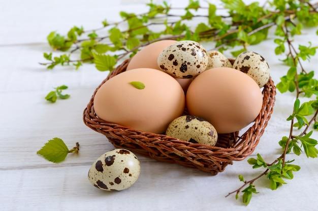 チキンとウズラの卵、白い木製の背景に緑の若い枝が付いているバスケット。イースター春の背景。