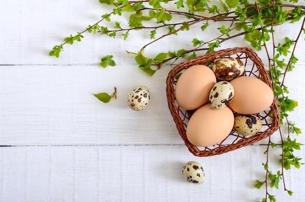 チキンとウズラの卵、白い木製の背景に緑の若い枝が付いているバスケット。上面図。イースター春の背景。