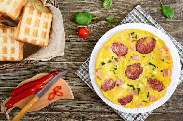 ハム、サラミ、チーズ、木製の背景に皿の上の緑のオムレツ。朝ごはん。上面図。