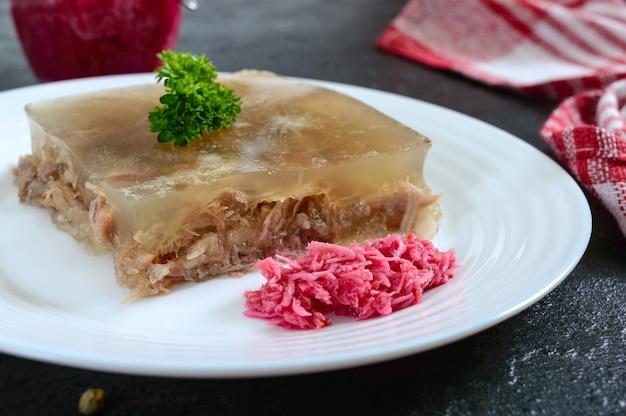 Мясо желе с острым хреном на белом фоне на черном фоне. славянское традиционное холодное блюдо. крупный план