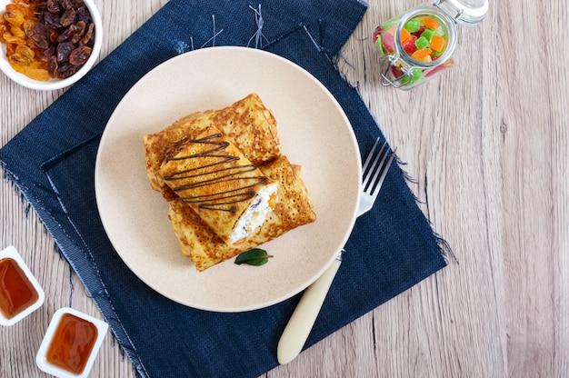 カッテージチーズ、バニラ、レーズンの皿に美味しい繊細なパンケーキ。健康的な朝食。上面図。
