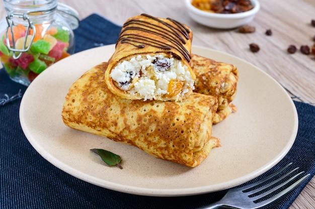 カッテージチーズ、バニラ、レーズンの皿に美味しい繊細なパンケーキ。健康的な朝食。