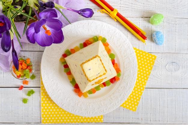 砂糖漬けの果物と休日明るい背景に春の花クロッカスの伝統的な豆腐イースターケーキ。