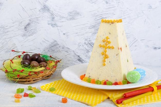 Традиционный творожный кулич с цукатами и шоколадные яйца на светлом фоне праздник.