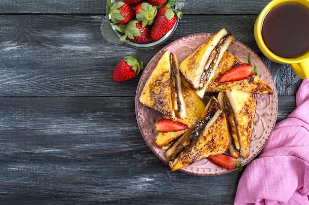 Сладкие французские тосты с бананом, шоколадом, клубникой на деревянной поверхности. вкусный завтрак. вид сверху