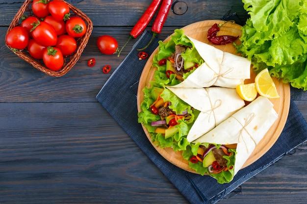 Буррито с нарезанным мясом, авокадо, овощами, острым перцем на тарелку на фоне темных деревянных. фаршированные лепешки. традиционная мексиканская закуска. вид сверху.