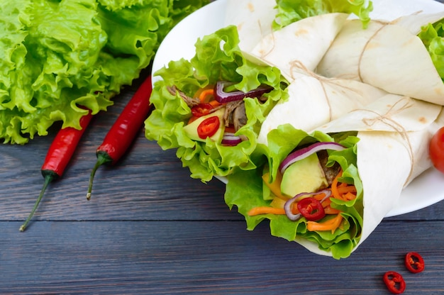 Буррито с нарезанным мясом, авокадо, овощами, острым перцем на тарелку на фоне темных деревянных. фаршированные лепешки. традиционная мексиканская закуска.
