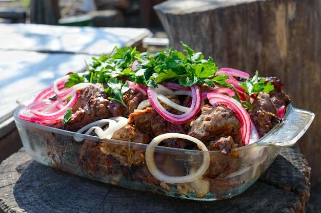 Мясо обжаривают на шпажках на открытом огне с маринованным луком и зеленью на фоне природы. шашлык. пикник