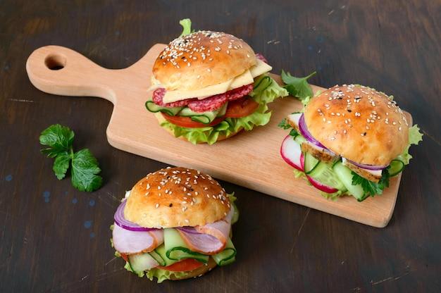 木の板に別のハンバーガー。自家製パン、ハム、肉、サラミ、野菜、ハーブ。ランチのサンドイッチ。