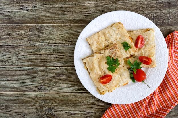 キノコ、カッテージチーズ、木製の背景の白いプレート上のチーズのパイ、キャセロールピタ。レイヤーケーキ。トップビュー