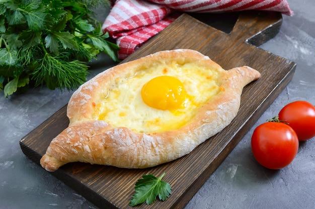 Хачапури по-аджарски. традиционная грузинская и армянская кухня. открытый пирог с сыром сулугуни и яичным желтком в виде лодочки на деревянной доске