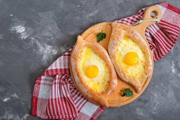 アジャリアンのカチャプリ。伝統的なグルジア料理とアルメニア料理。木の板にボートの形でスルグニチーズと卵黄のパイを開きます。トップビュー