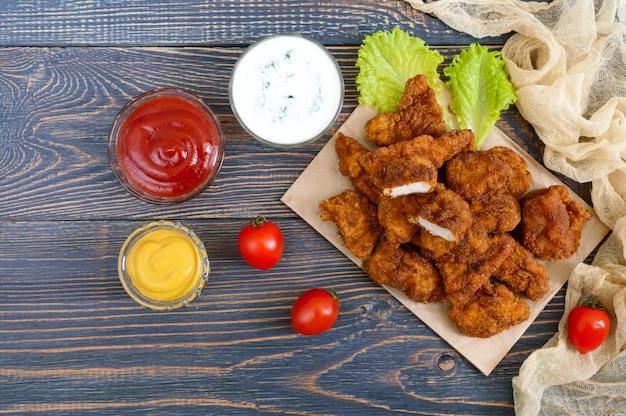 Куриные наггетсы. кусочки жареного хрустящего мяса, на бумаге с различными соусами на деревянном столе. традиционная закуска.