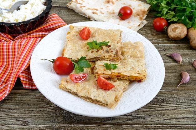 キノコ、カッテージチーズ、木製の背景の白いプレート上のチーズのパイ、キャセロールピタ。レイヤーケーキ。