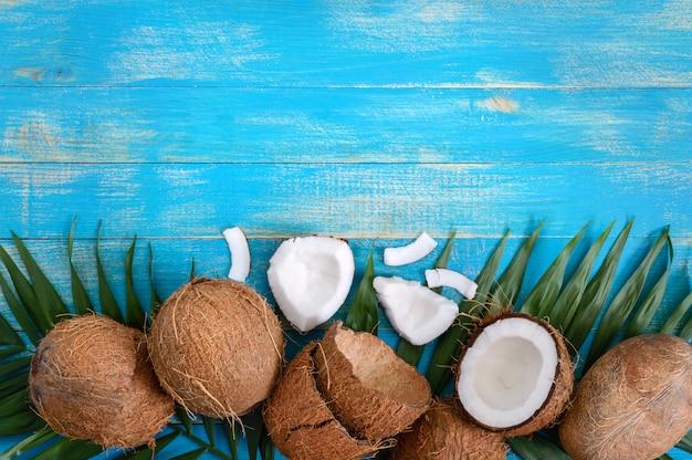 青い木製の背景に全体のココナッツ、シェル、緑のヤシを葉します。コピースペース。平面図、フラットレイアウト。熱帯の背景。