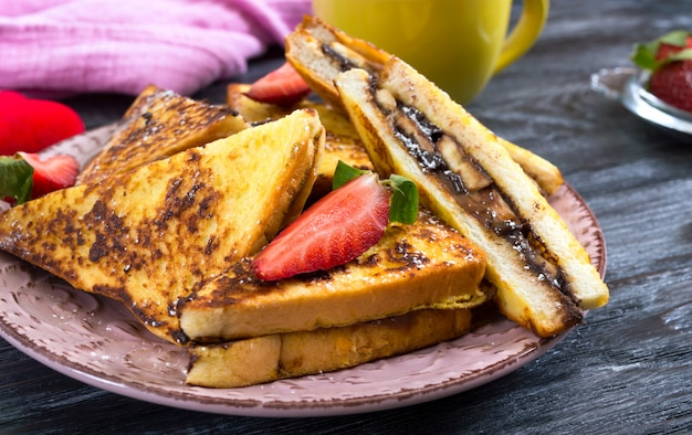 Сладкие французские тосты с бананом, шоколадом, клубникой на деревянной поверхности. вкусный завтрак
