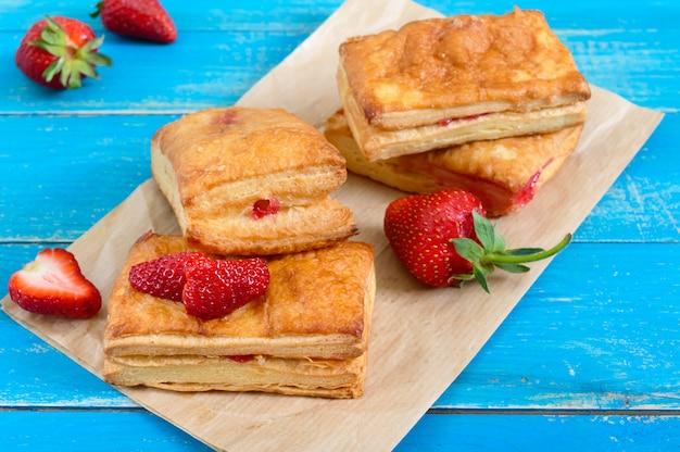 Сладкий вкусный десерт из слоеного теста на деревянных фоне. вкусное домашнее печенье с клубничным джемом, ягодами и сахарной пудрой.