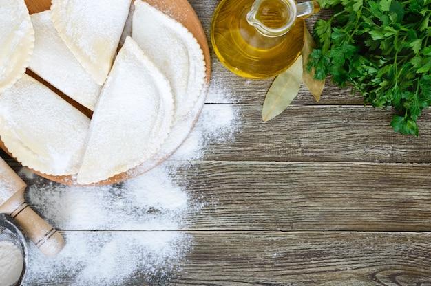 木製のテーブルの上に小麦粉で揚げたチェブレクではありません。伝統的なチュルクモンゴル料理。冷凍半製品。碑文の空き容量。