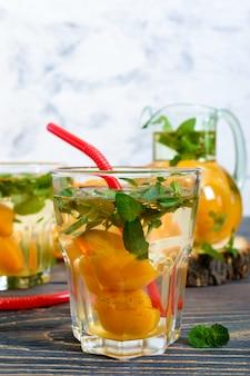 夏の冷たい飲み物。アプリコットと木製のテーブルにグラスにミントのおいしいさわやかなドリンク。果物のコンポート。セレクティブフォーカス。