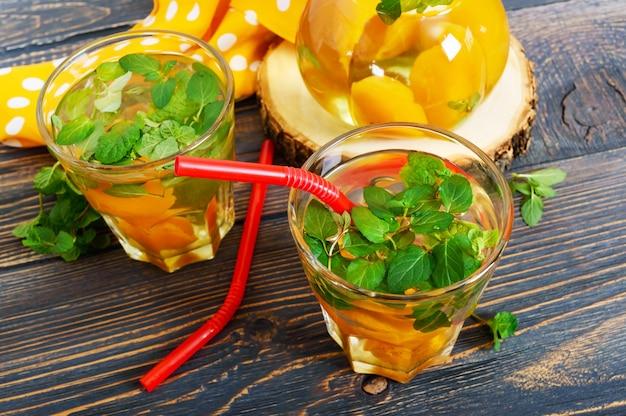 夏の冷たい飲み物。アプリコットと木製のテーブルにグラスにミントのおいしいさわやかなドリンク。果物のコンポート。