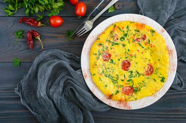 フリタータ。木製の背景の白いプレートにトマト、チーズ、緑とイタリアのオムレツ。