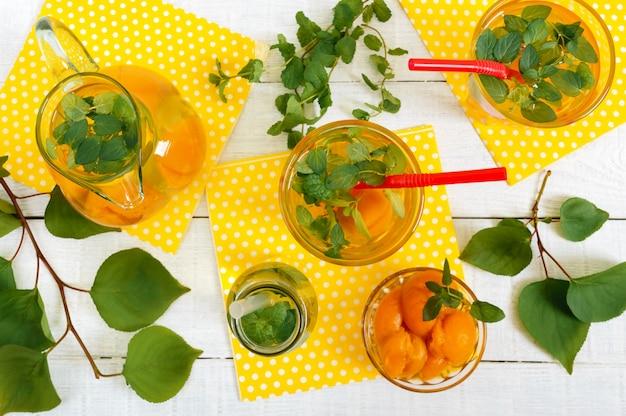 夏の冷たい飲み物。アプリコットと白い木製の背景にグラスにミントのおいしいさわやかなドリンク。果物のコンポート。トップビュー
