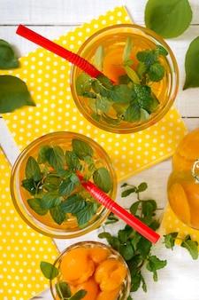 夏の冷たい飲み物。アプリコットと白い木製の背景にグラスにミントのおいしいさわやかなドリンク。果物のコンポート。