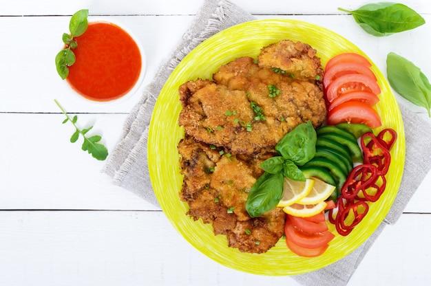 シュニッツェルと野菜、白い木製のテーブルのトマトソース。上面図。